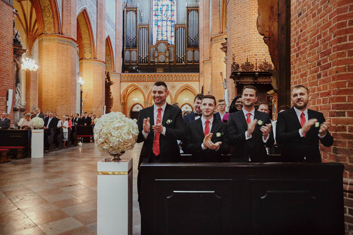 ślub w kościele - drużbowie biją brawo