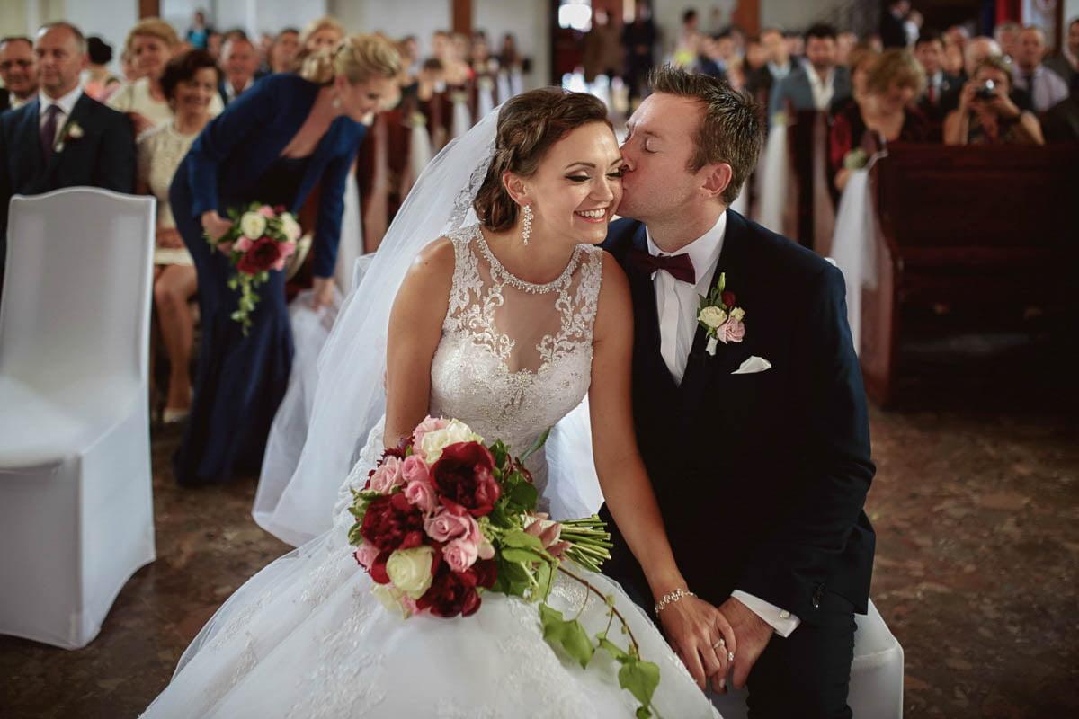 ceremonia ślubna - pocałunek przy ołtarzu przed weselem w Folwarku Wirówek