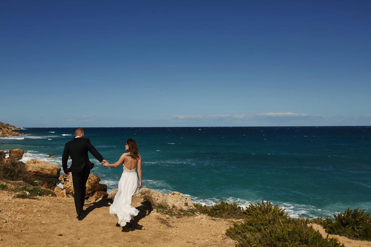 zdjecia ślubne malta - Ramla Bay - para idze za rękę