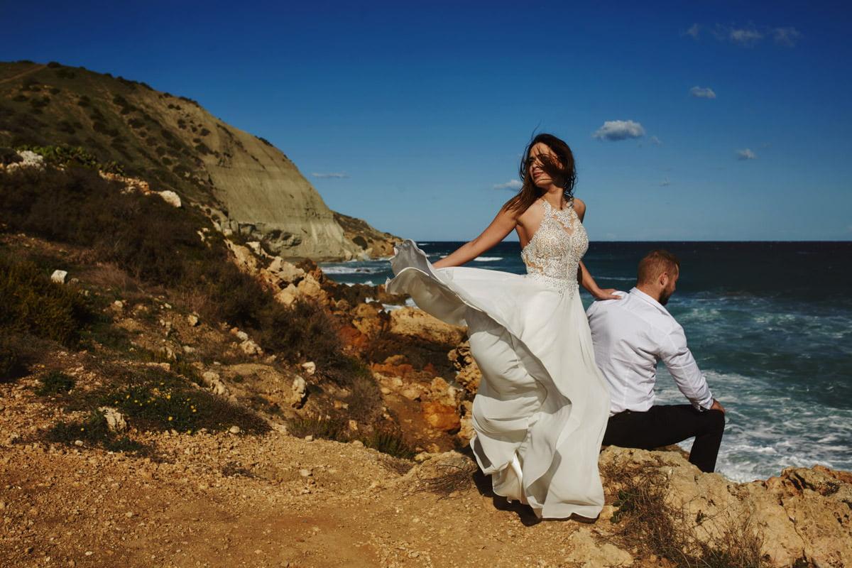 zdjecia ślubne malta - Ramla Bay - rozwiana suknia ślubna