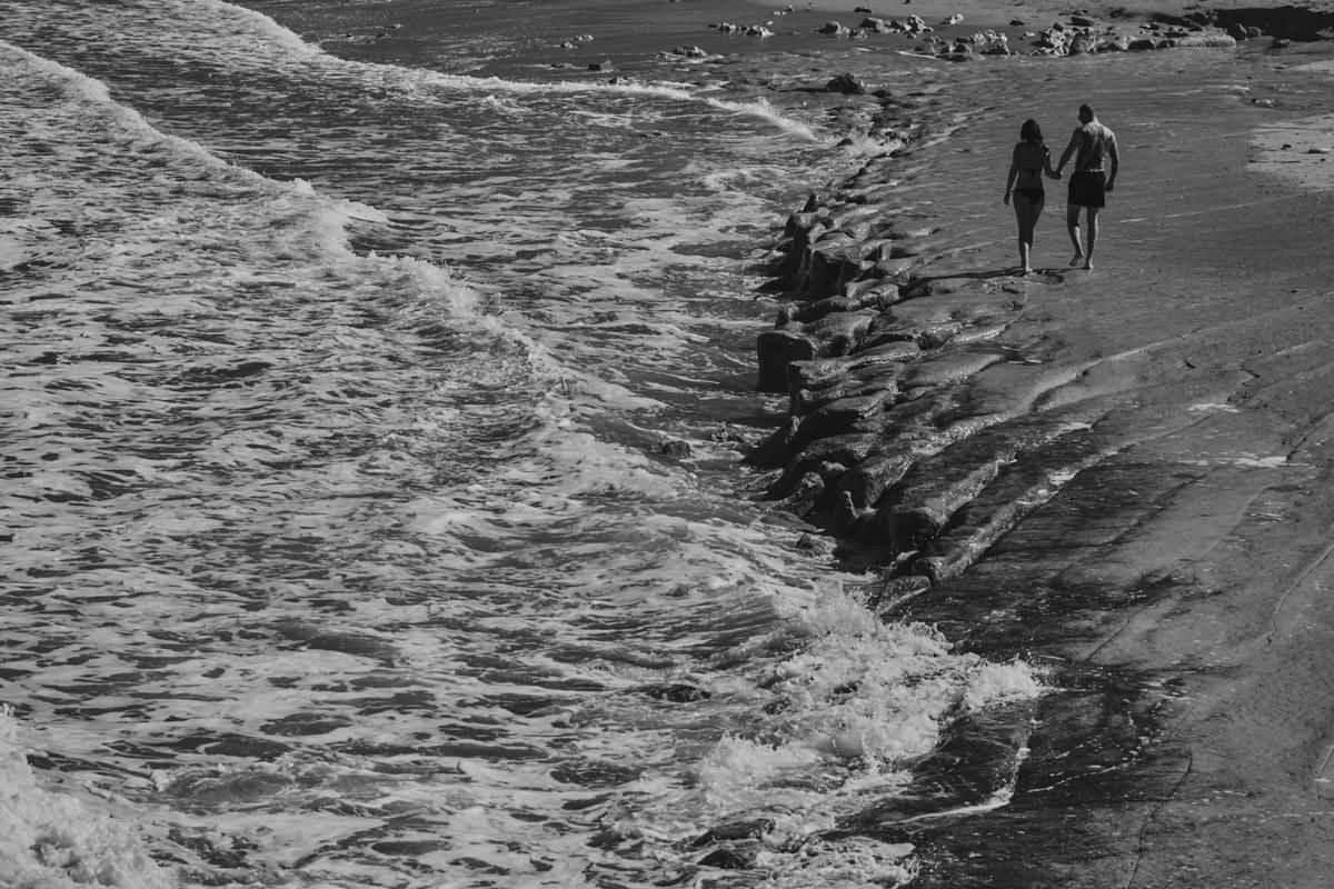 zdjecia ślubne malta - Ramla Bay - spacerująca para ludzi