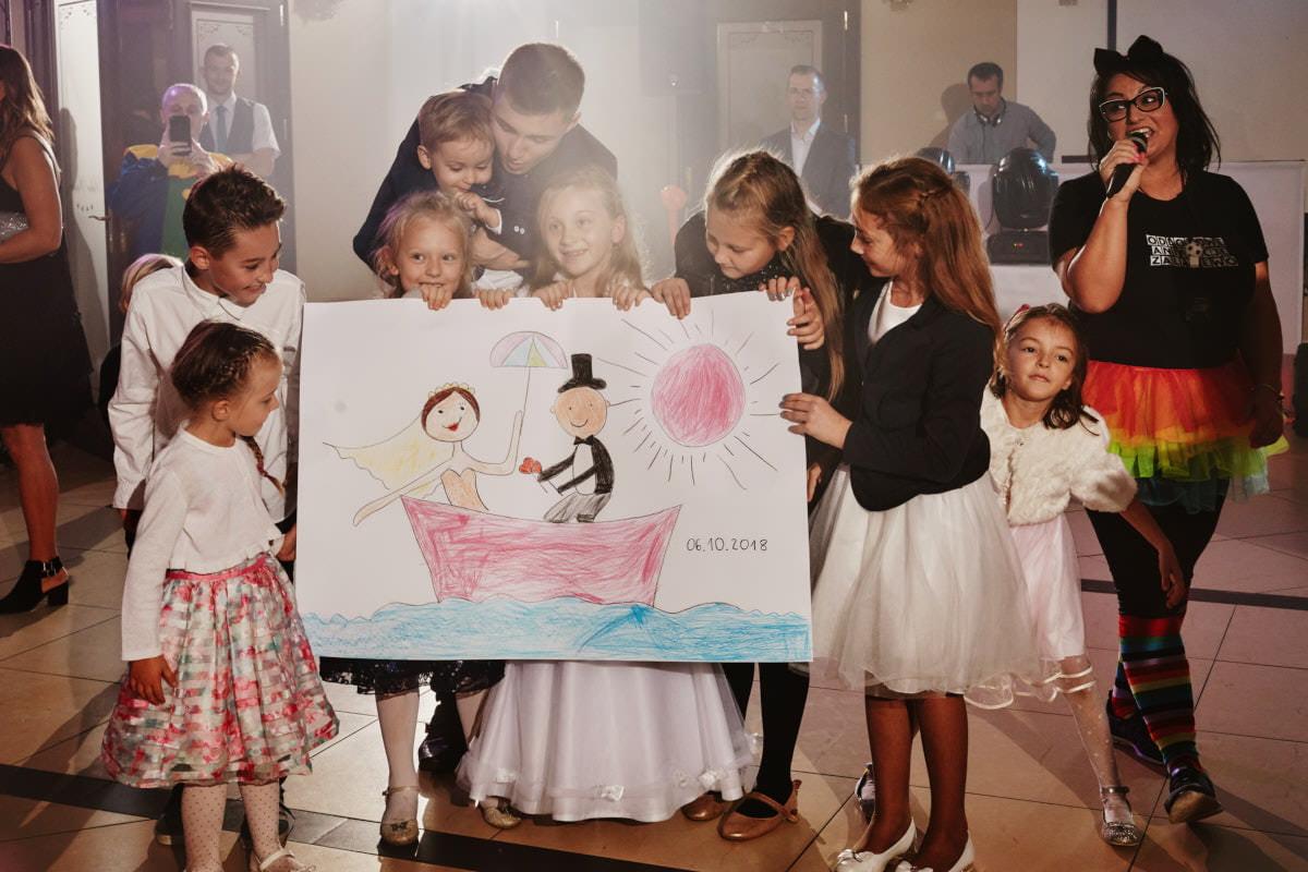 dziecie dają prezent Państwu Młodym